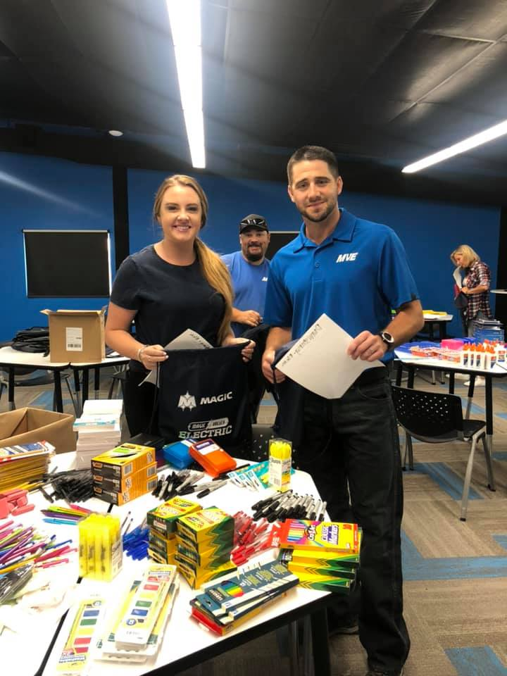 A Magic Valley Electric LLC with a member of a local charity receiving art supplies