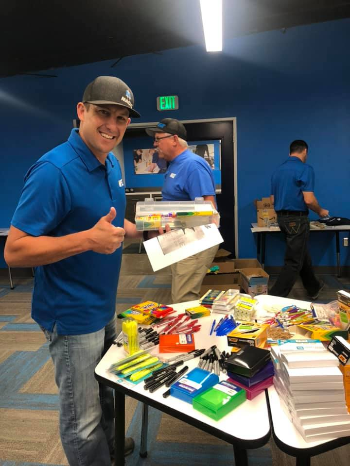 A member of the Magic Valley Electric LLC giving a thumbs up while gathering art supplies